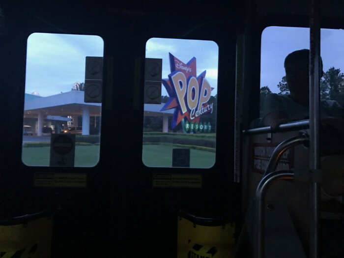 inside Disney bus with view through window of Disney's Pop Century Resort sign