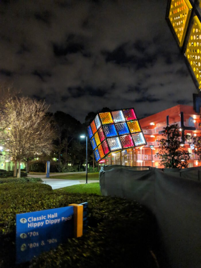 Disney's Pop Century Resort at night with giant Rubik's Cube & sign for Classic Hall, Hippy Dippy Pool, 70s, 80s, 90s sections