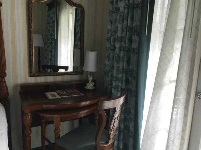 Picture of curtains, desk, mirror, lamp & bed at Disney's Boardwalk Inn