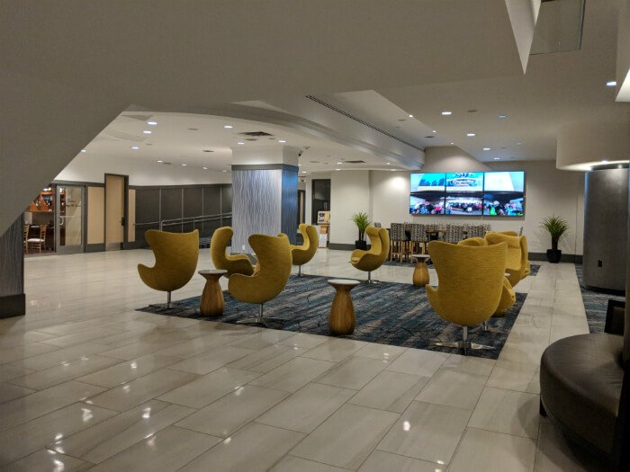 Wyndham Grand Pittsburgh Downtown lobby with yellow chairs, several TVs and open space