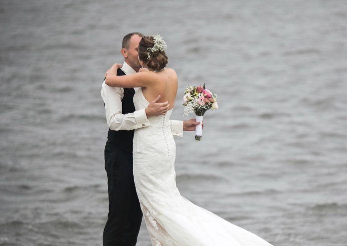 Best wedding venues in Ohio. Picture of a groom & bride kissing by a lake.