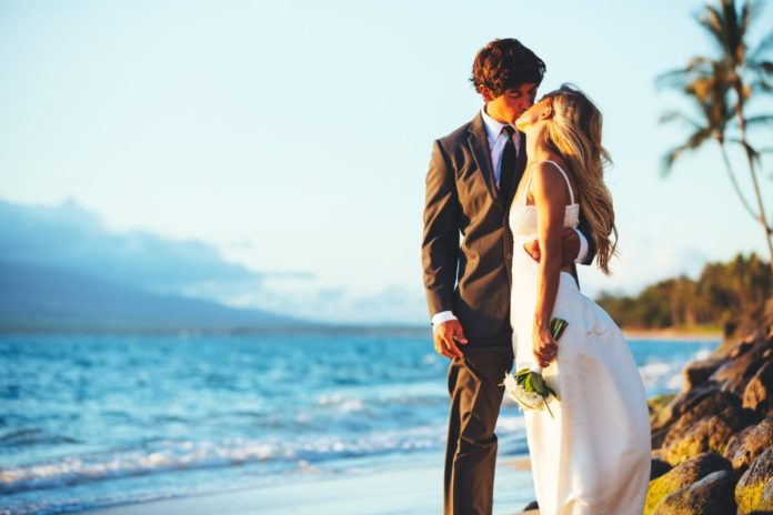 Picture of a bridge & groom kissing on the beach. Find out the best Hawaiian resorts for a wedding.