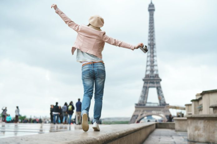 Picture of a happy tourist visiting Paris, France. Find out how you can get a free trip to Paris