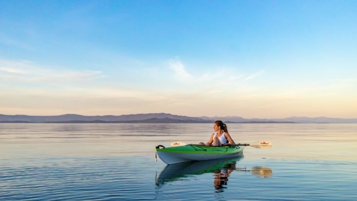 A picture of a woman kayaking at Qualicum Beach on Vancouver Island in British Columbia. Find out the area's best hotels
