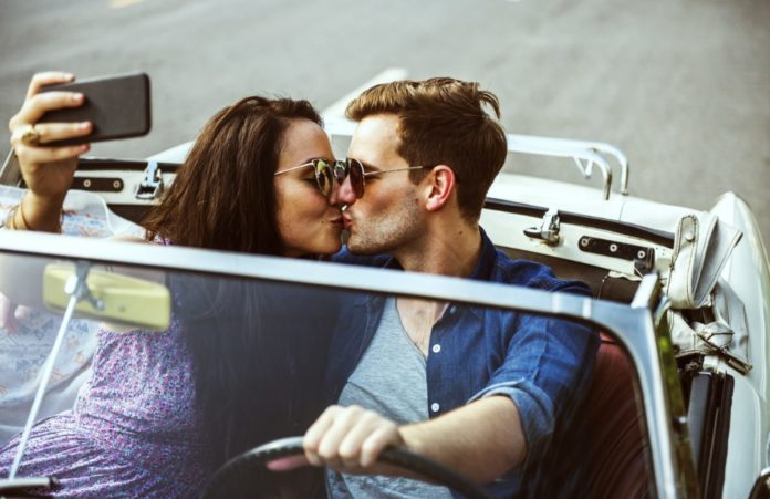 Couple Driving a Car Traveling on Road Trip Together. Learn how to get a free road trip.