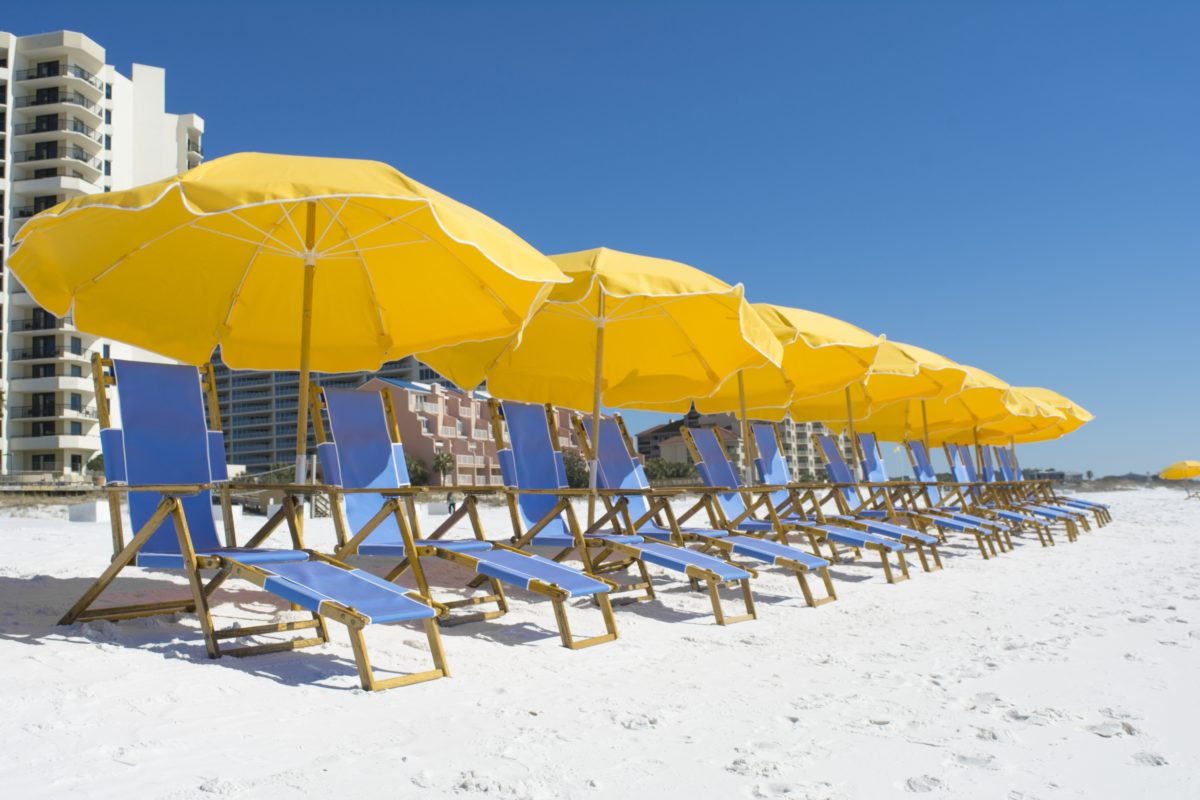 Relax on the beach under an umbrella when staying at Hilton Sandestin Beach Golf Resort & Spa
